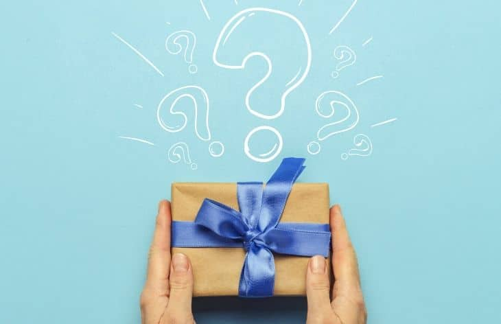 A paper-wrapped gift with a blue bow with a question mark above it.