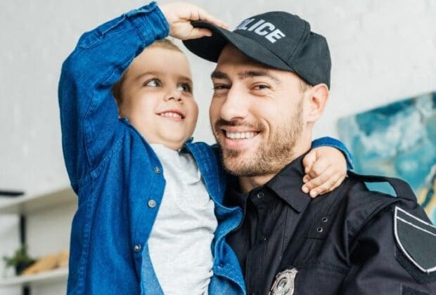 A police officer and his son smiling together as his son plays with his hat.
